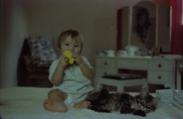 Dan seated on the bedspread of my parents old bedroom with the cat (Tigger?).