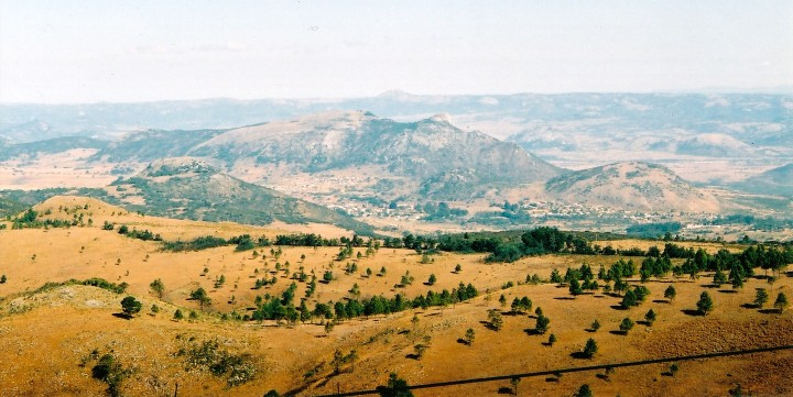 The pine-studded grassland plateau flanking the mountains.