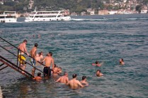 Boys and men dip into a swiftly flowing Bosphorus near Bebek.