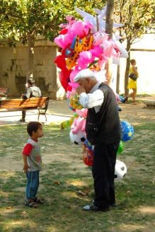 A young boy waits expectantly for this vendor to inflate a balloon for him.