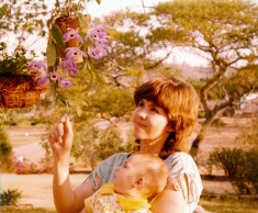 My mother with baby Dan looks at a quite stunning orchid on the patio. Take note of the old, spreading acacia in the background.