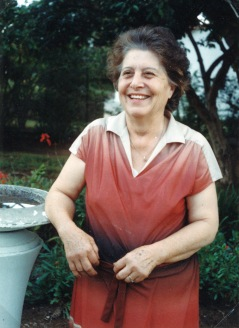 My paternal grandmother or Yia- Yia leaning against a bird bath in her front garden, Marondera.