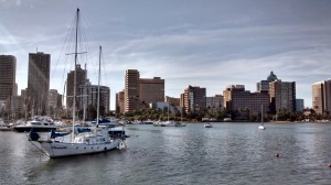 The view across Durban harbour from a pier with the city skyline as a backdrop.