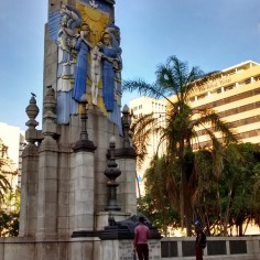 Two young black men, students possibly, look up with interest at this restored monument to the Great War in central Durban near the Town Square.